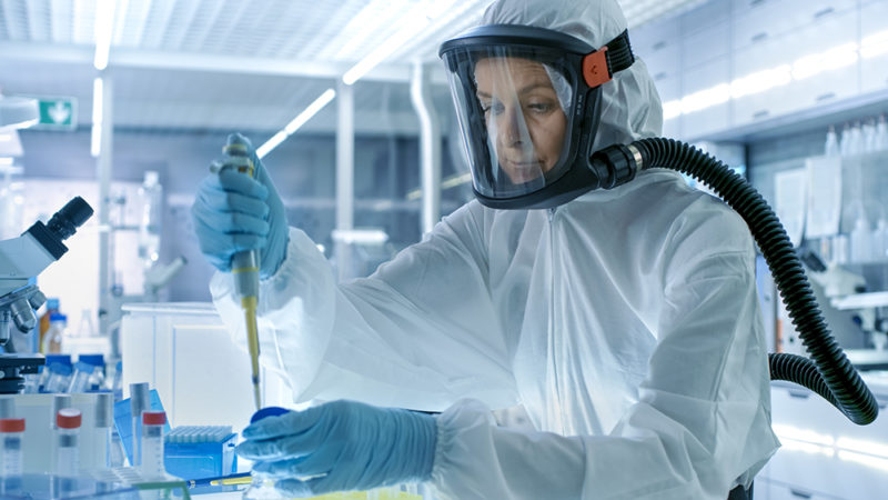 Medical Virology Research Scientist Works in a Hazmat Suit with Mask, She Uses Micropipette. She Works in a Sterile High Tech Laboratory, Research Facility.