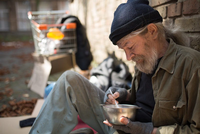 Close up view of homeless man sitting by the brick wall, eating. Homeless man with his belongings living in the street.