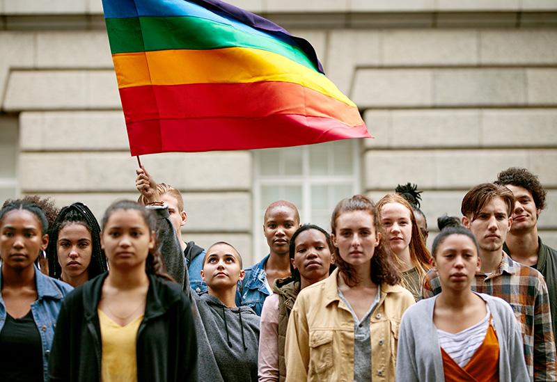 LGBTQI community with flag on city street