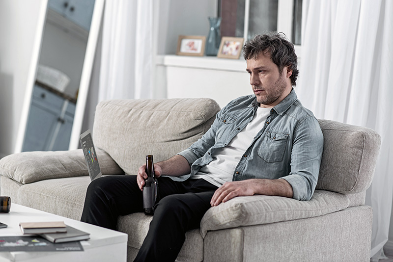 Depression. Unshaven depressed man sitting on a soft sofa with a laptop by his side and drinking alcohol after losing his job