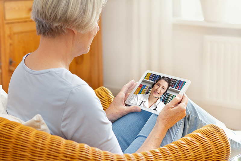 Senior woman using tablet computer for telehealth appointment