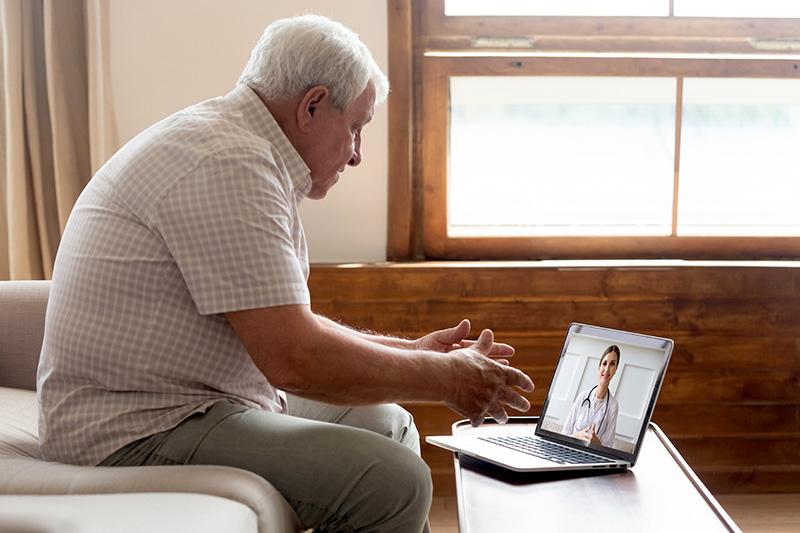 Elderly man make telehealth video call communicating with doctor online