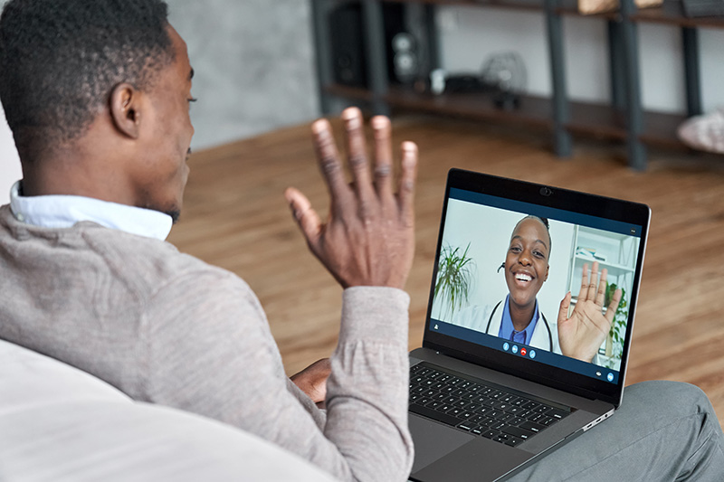 Male African American patient on telehealth conference video call with female online doctor.