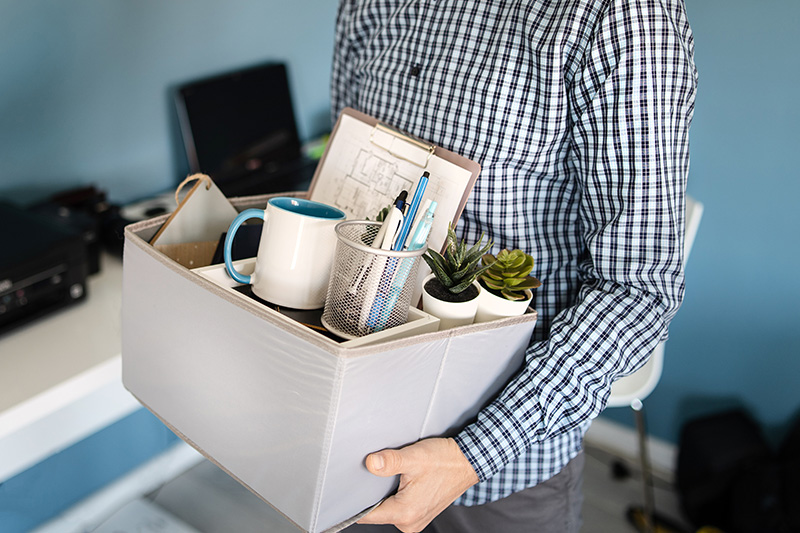 man holding a box with personal items leaving the office after being fired from work due recession economic crisis downturn